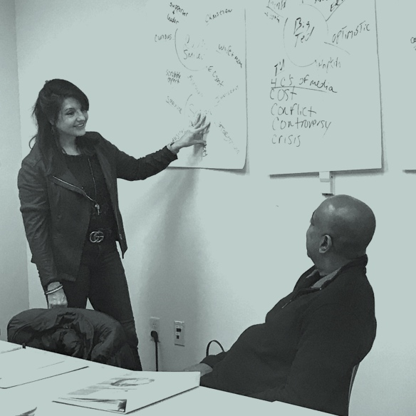 sharon pointing to white board and don listening