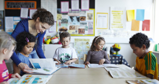 Teacher looking in books with diverse group of children in a classroom