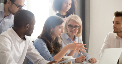 Female mentor teaching diverse group of employees at an office table.