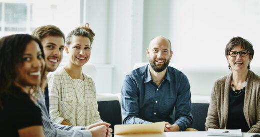 Smiling group of businesspeople in team meeting in office conference room