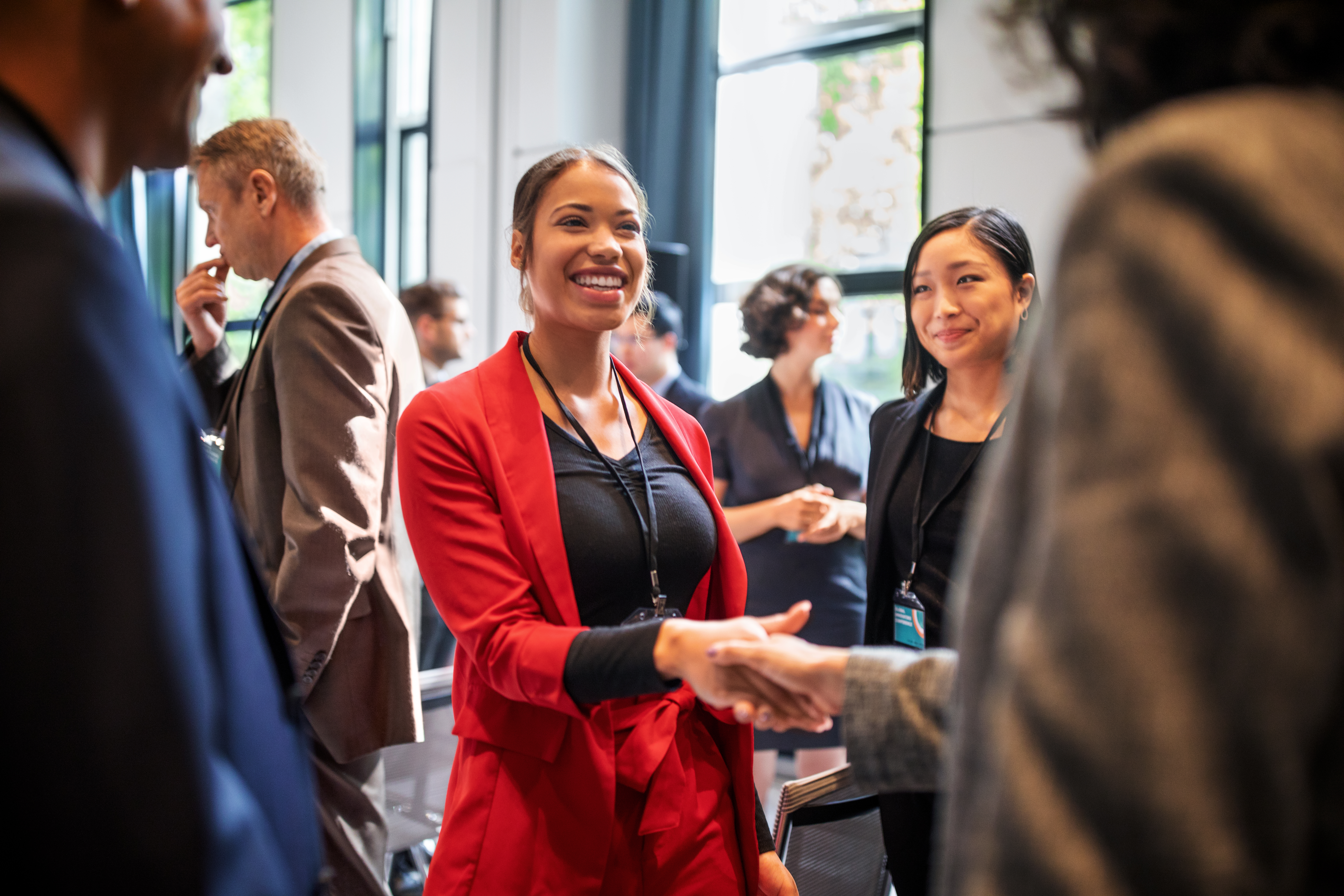 Confident businesswomen handshaking while standing in corridor of an auditorium. Female professionals greeting each other convention center.