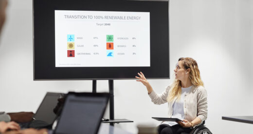 Confident businesswoman on wheelchair explaining presentation. Disabled female executive is gesturing while looking at screen. She is in smart casuals at board room in office.