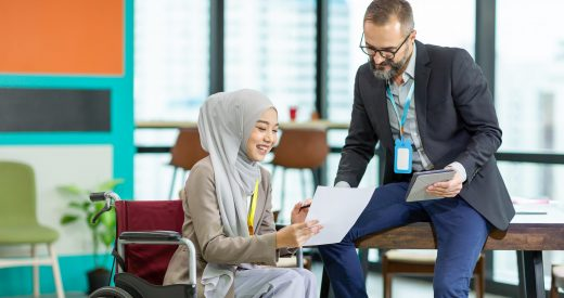 Asian Muslim businesswoman sitting on wheelchair presenting business graph on paper to manager. Smiling group of diverse corporate colleagues in the modern office. Diversity or multicultural in office