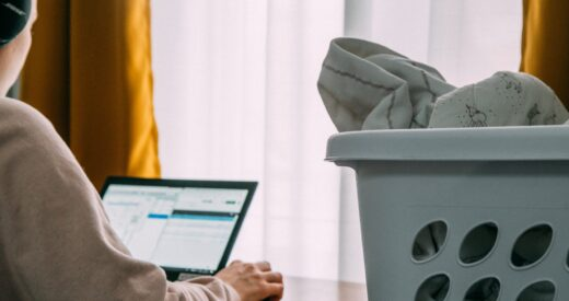woman working from home and doing laundry beside her