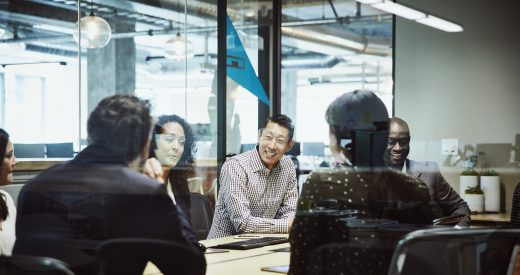 Smiling businessman leading client meeting in office conference room