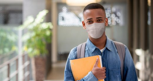 Portrait of an African American student wearing a facemask at school whole holding a notebook and looking at the camera - COVID-19 lifestyle