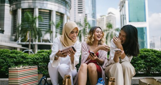 Multi-ethnic group of women sitting in front of the Petronas towers, using their smart phones, Kuala Lumpur, Malaysia