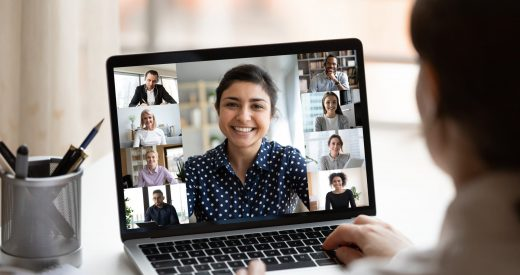 Woman sitting at a desk looking at computer screen with a collage of diverse people in a webcam view.